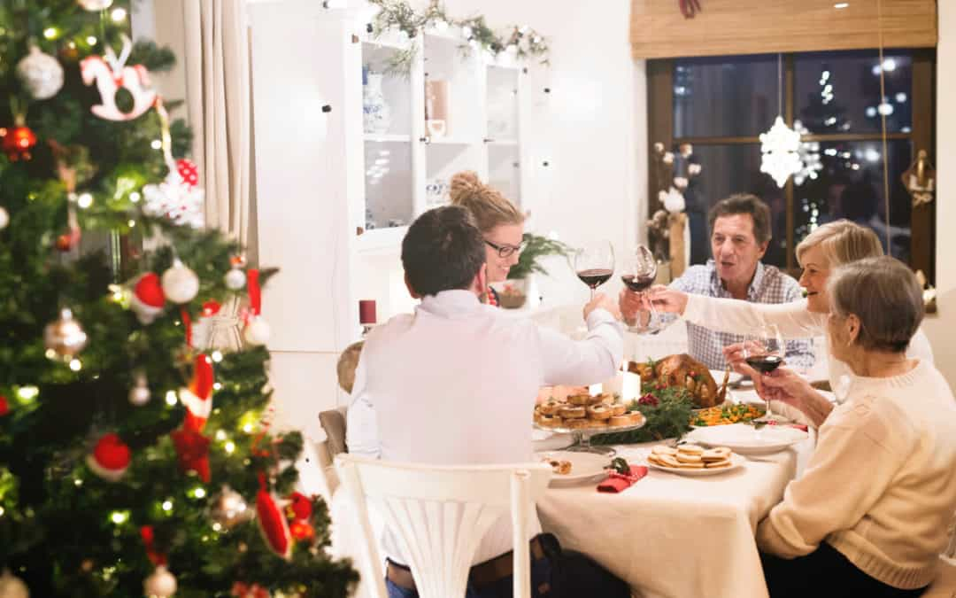 graphicstock beautiful big family sitting at the table celebrating christmas together at home illuminated christmas tree behind them Bd 5Ca3rMW 2 2 scaled
